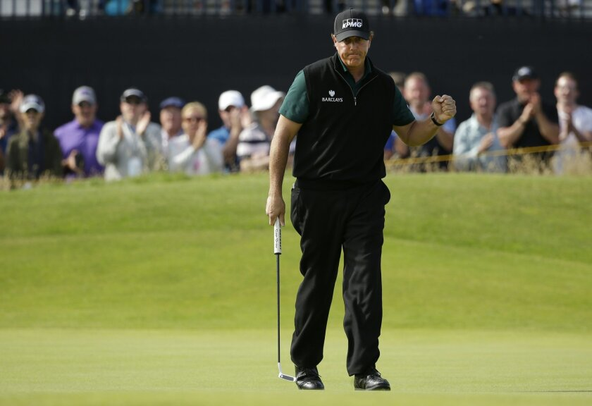 Phil Mickelson of the United States celebrates and the crowd applaud after he made a birdie put on the 14th green during the first round of the British Open Golf Championship at the Royal Troon Golf Club in Troon, Scotland, Thursday, July 14, 2016. (AP Photo/Matt Dunham)
