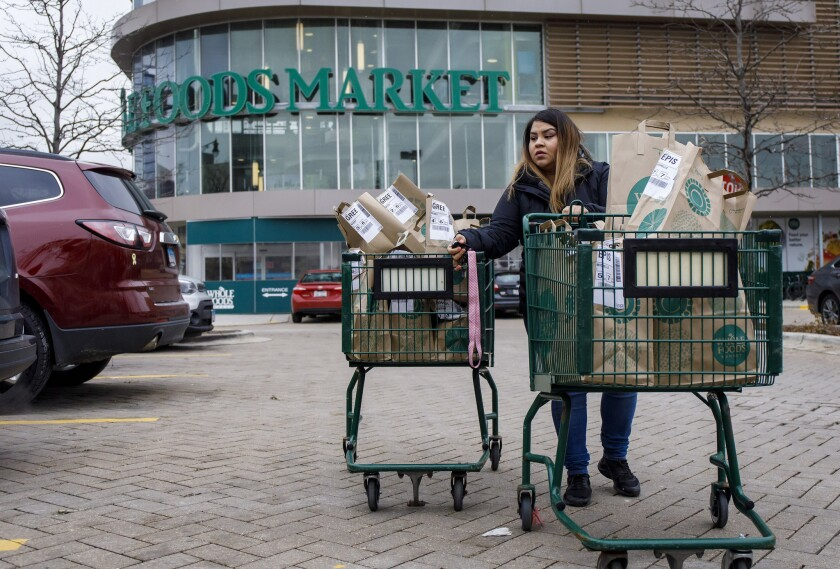 An Instacart worker transports orders for three customers to her car.