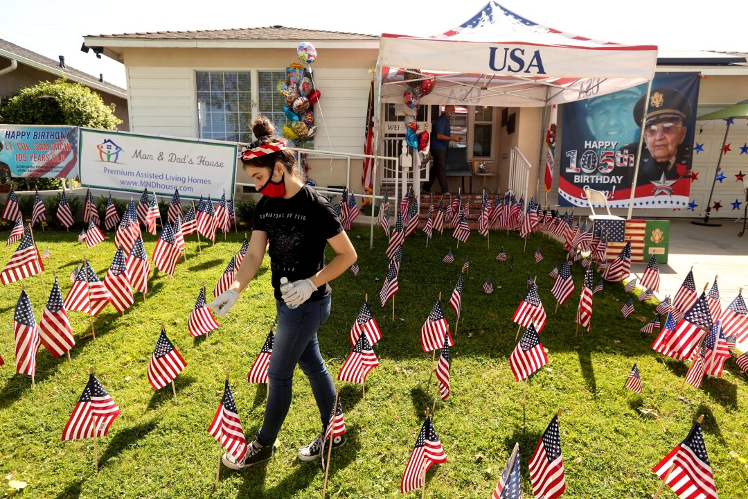 Isabella Leader, 15, counts the American flags left for World War II veteran Lt. Col. Sam Sachs at Mom & Dad's House in Lakewood on April 26.