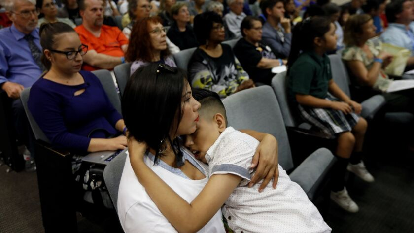 LOS ANGELES, CA AUGUST 21, 2018: Perla Esparza, left, holds her son Joshua Del Campo, 12, both of