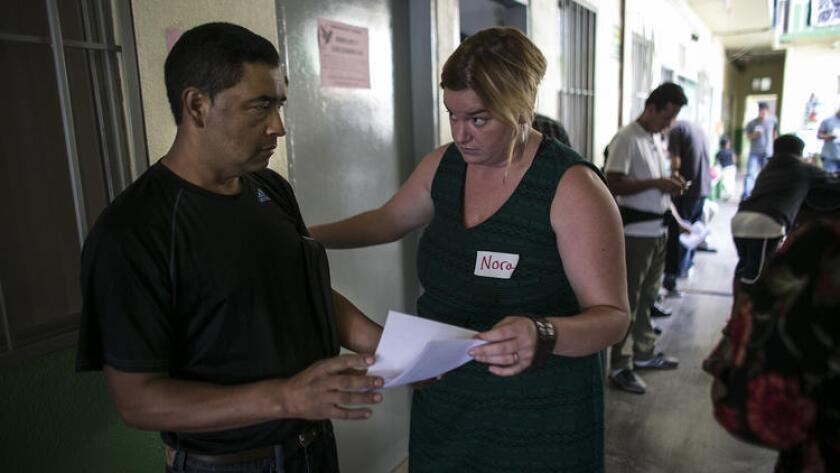La abogada Nora Phillips, ofrece ayuda a un migrante en un refugio en Tijuana.