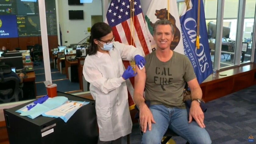 """In this image taken from live streamed video from the California Governor's Office, California Gov. Gavin Newsom getting a flu shot during a news conference on Monday, Sept. 28, 2020, in Rancho Cordova, Calif. Newsom said he has gotten a flu shot every year """"for as long as I can remember."""" He said it's important to get a flu shot this year to ensure hospitals are not overrun by a combination of flu and coronavirus cases. While California's coronavirus cases have been decreasing over the last several weeks, Newsom said Monday there is """"some concern"""" that cases could increase over the next few weeks. (California Governor's Office via AP))"""