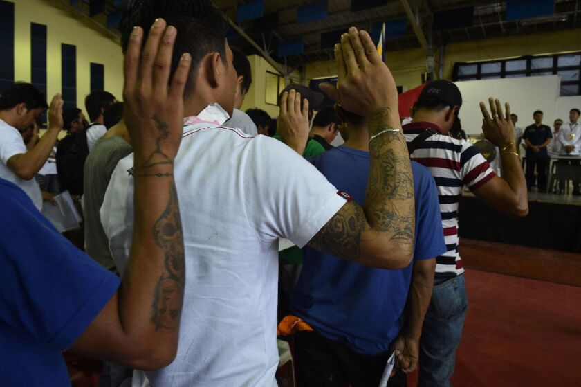 Drug users and dealers take an oath on July 18 after they voluntarily surrendered to authorities in Tanauan town, Batangas province, south of Manila.