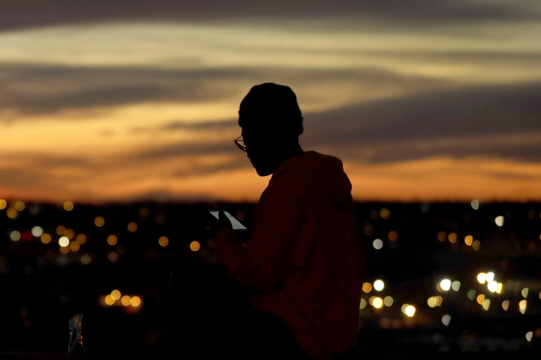 A person looks at a smart device as the sun sets in Kansas City, Mo. Technology has helped enable social distancing.