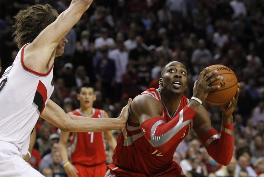 Rockets center Dwight Howard looks to score against Trail Blazers center Robin Lopez in the second half of their playoff game Friday night in Portland.