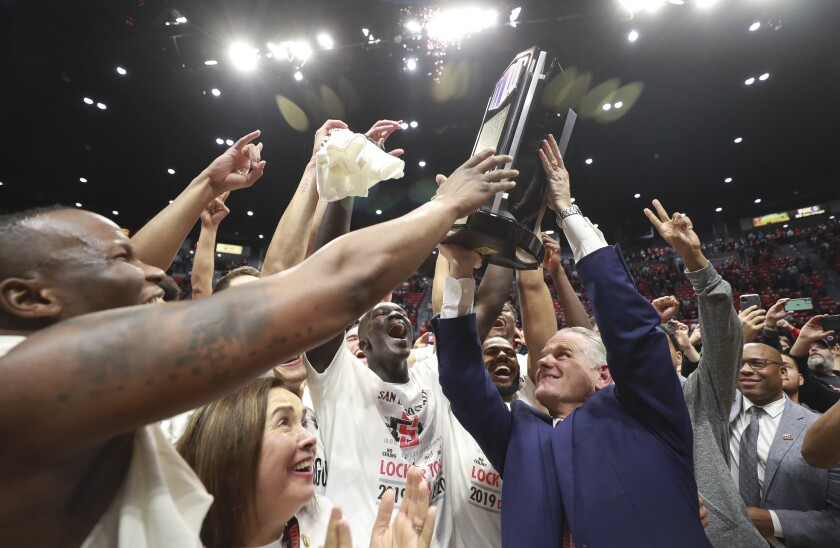 Aztecs coach Brian Dutcher lifts up Mountain West trophy after SDSU defeated New Mexico 82-59 on Feb. 11 at Viejas Arena.