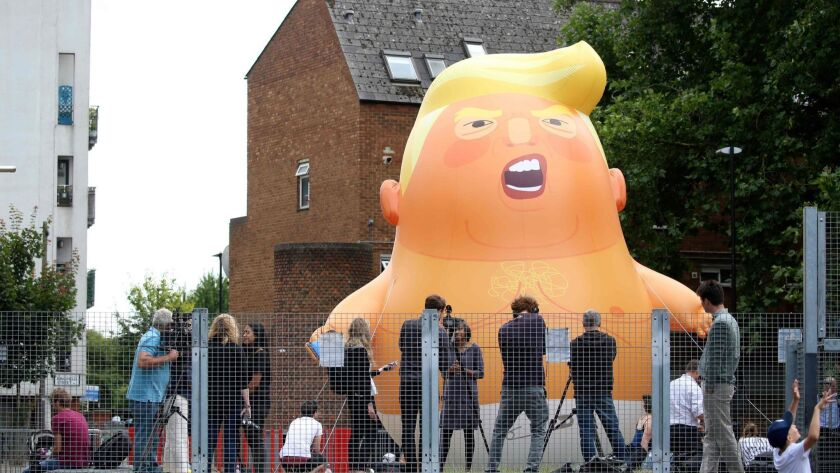 Activists in London inflate a giant balloon depicting U.S. President Trump as an orange baby on July 10, 2018, ahead of his visit.