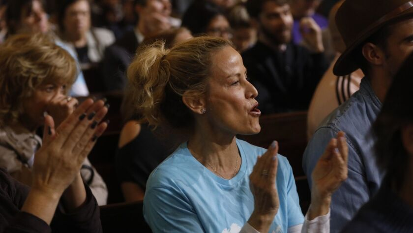LOS ANGELES, CA - DECEMBER 11, 2018 - - Airbnb supporters Tami Smith, center, applauds a speaker who