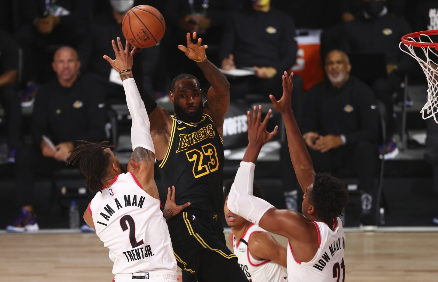 Portland Trail Blazers guard Gary Trent Jr., left, and center Hassan Whiteside try to stop Lakers forward LeBron James.
