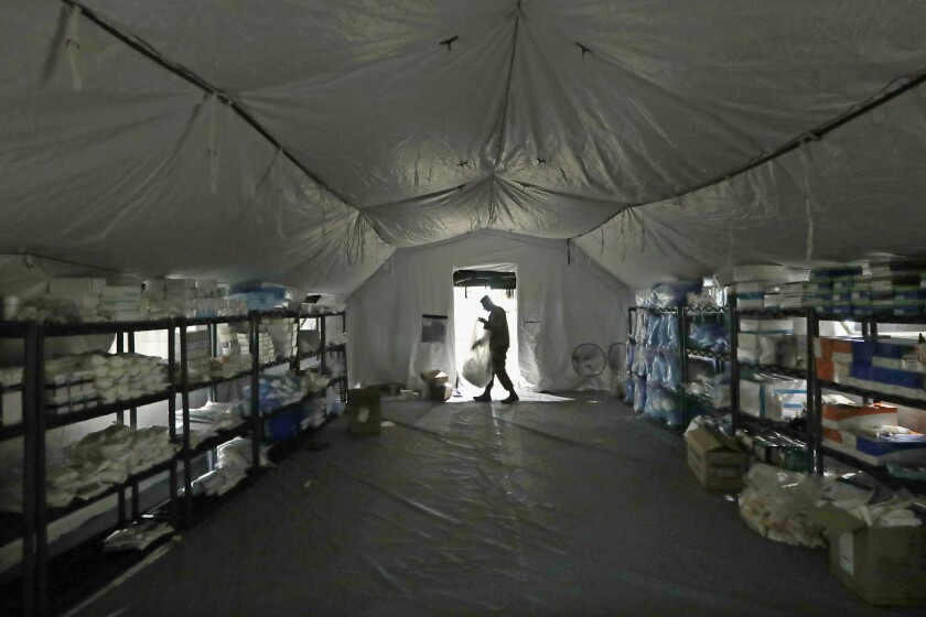 FILE - In this March 31, 2020, file photo a U.S. Army soldier walks inside a mobile surgical unit being set up by soldiers from Fort Carson, Col., and Joint Base Lewis-McChord (JBLM) as part of a field hospital inside CenturyLink Field Event Center, in Seattle. Military suicides have increased by as much as 20% this year compared to the same period last year, and some incidents of violent behavior have spiked, as service members struggle with isolation and other impacts of COVID-19 added to the pressures of war-zone deployments and responding to national disasters and civil unrest. (AP Photo/Elaine Thompson, File)