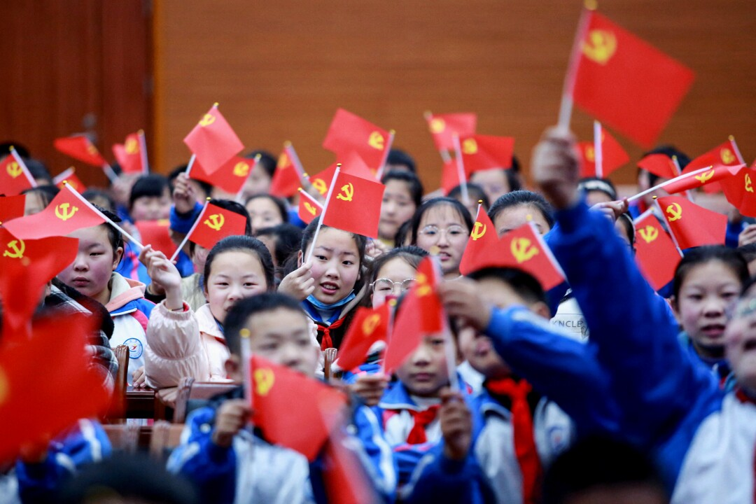 A big group of children wave red flags bearing yellow hammer and sickle symbol in corner