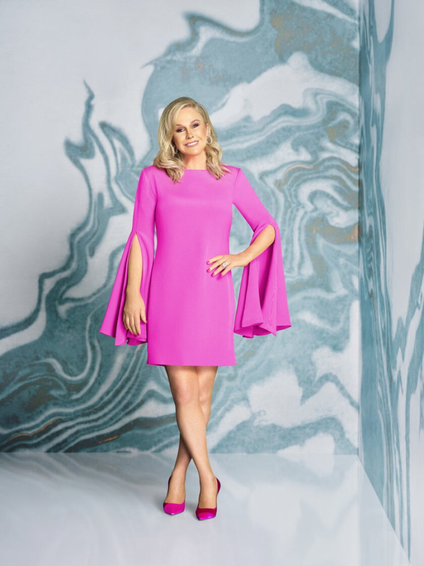 A woman poses in a pink dress