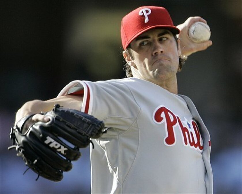 in this Aug. 17, 2008 file photo, Philadelphia Phillies starter Cole Hamels pitches against the San Diego Padres during the first inning of a baseball game  in San Diego. Hamels and the Phillies have reached an agreement on a three-year, $20.5 million contract extension, helping the left-hander av