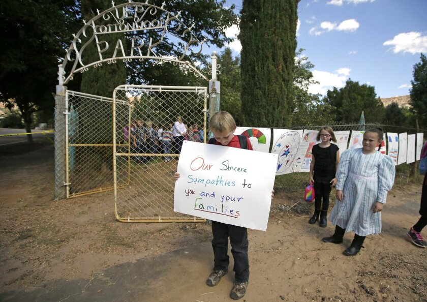 David Barlow, a student from the Cottonwood Elementary School, holds a sign as they erect a memorial Thursday, Sept. 17, 2015, in Colorado City,Ariz. The flood water swept away multiple vehicles in the Utah-Arizona border town, killing several people. (AP Photo/Rick Bowmer)