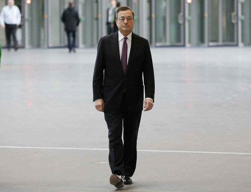 President of the European Central Bank Mario Draghi, walks in the lobby of the ECB headquarters two days ahead of a meeting of the governing council in Frankfurt, Germany, Tuesday, Jan. 19, 2016. (AP Photo/Michael Probst)