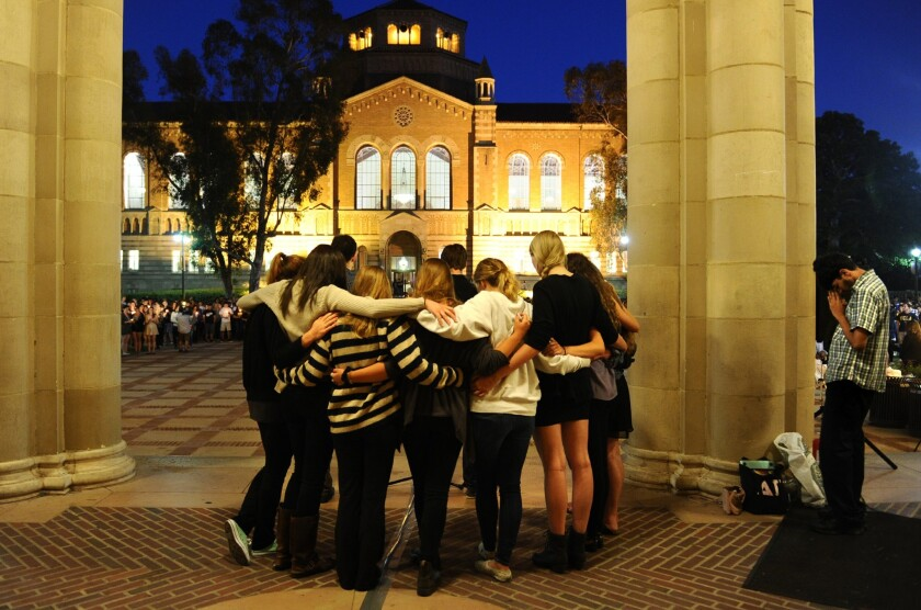 Students observe a moment of silence near Royce Hall at UCLA during a tribute to the Isla Vista victims.