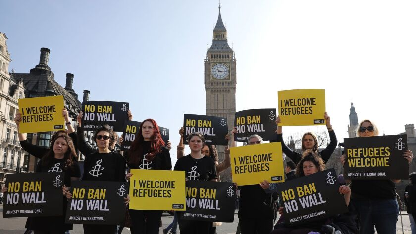 Amnesty International activists protest against President Trump's travel ban in Parliament Square on March 16, 2017 in London.