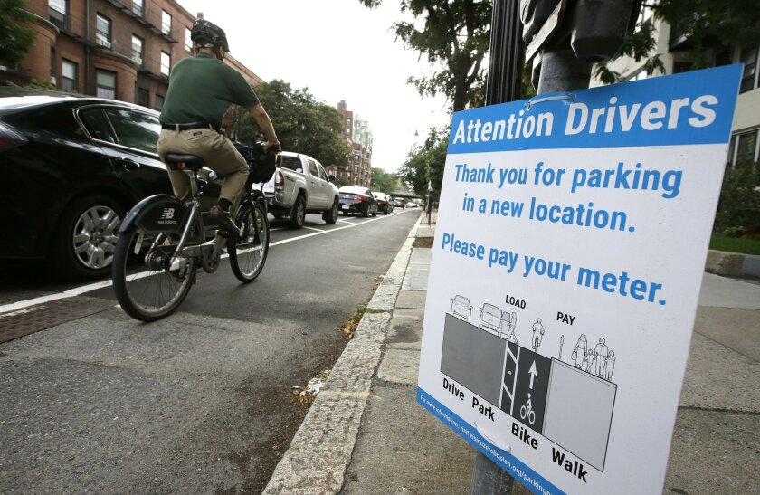 In this Tuesday, Aug. 16, 2016, photo, a cyclist rides in a bike lane between parked cars, left, and the sidewalk in Boston. Cities around the world are increasingly changing bike lanes to make them safer in light of fatal crashes involving cyclists and cars. (AP Photo/Steven Senne)