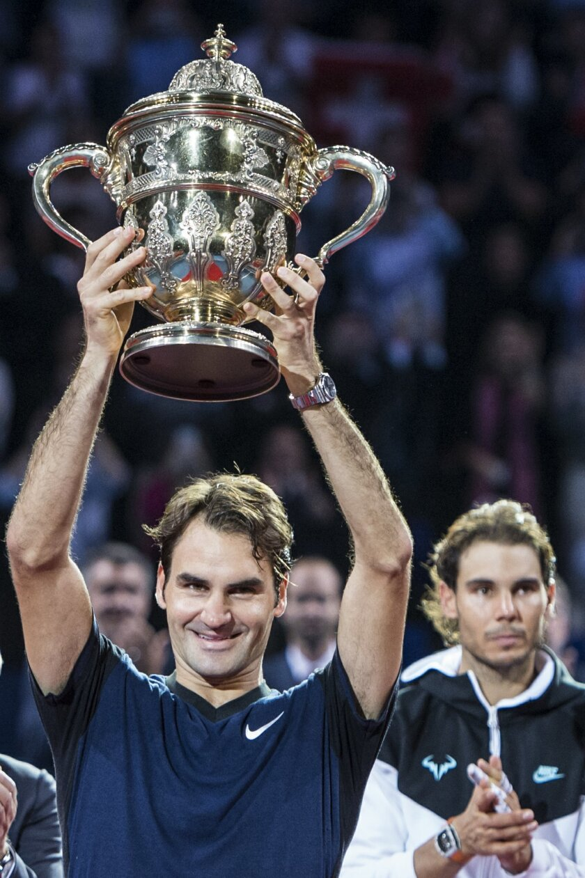 Switzerland's Roger Federer, left, poses with the trophy, next to Spain's Rafael Nadal, right, after their final match at the Swiss Indoors tennis tournament at the St. Jakobshalle in Basel, Switzerland, Sunday, Nov. 1, 2015. Federer won the match with 6-3, 5-7 and 6-3. (Dominic Steinmann/Keystone