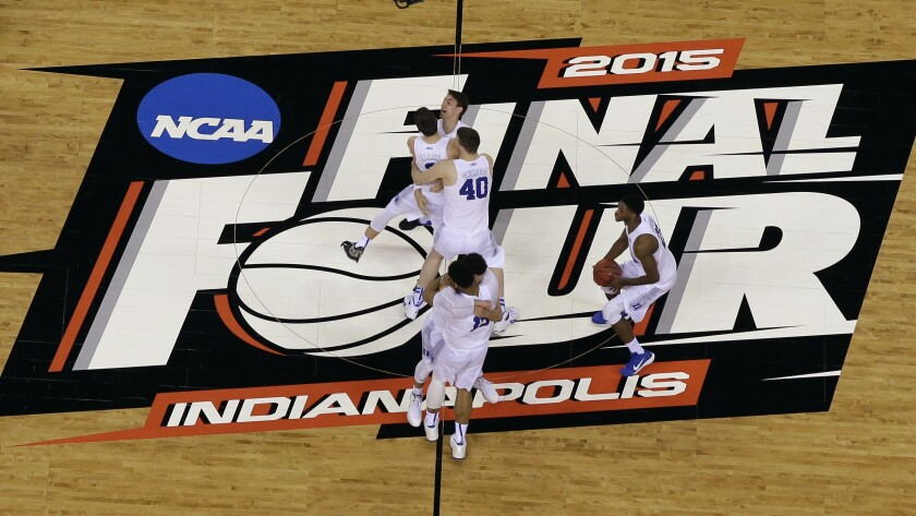 Duke players celebrate on the basketball court after winning the 2015 NCAA championship game.