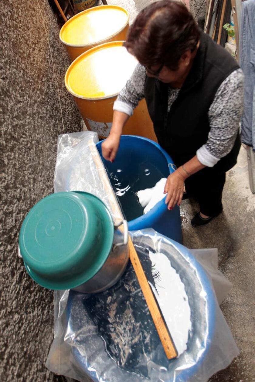 Una mujer acumula agua tras el corte por obras de mantenimiento en Ciudad de México (México). EFE