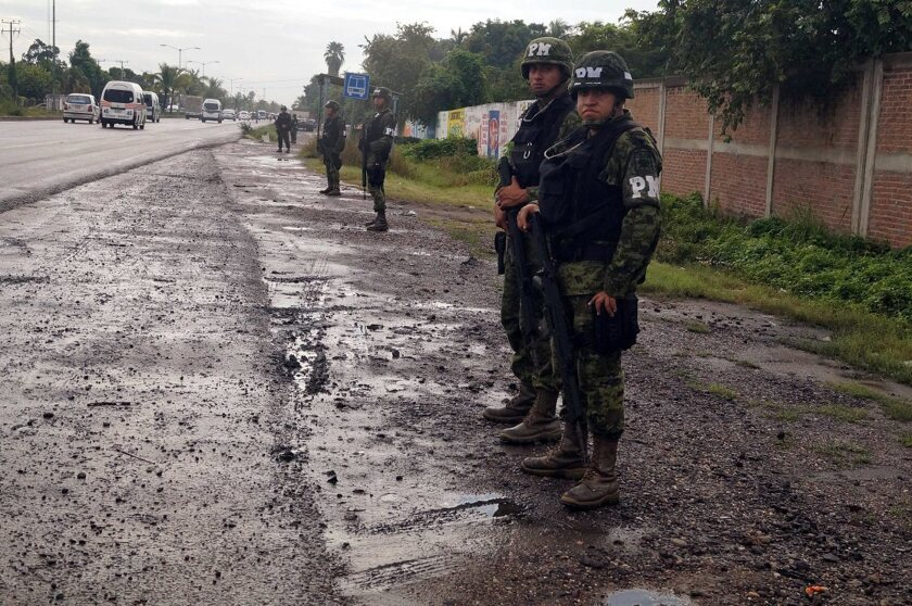 Federal troops take over the port of Lazaro Cardenas and the municipal police headquarters in Mexico's troubled Michoacan state in November. Authorities said Monday that the city mayor has been arrested and accused of kidnapping, extortion and links to organized crime.