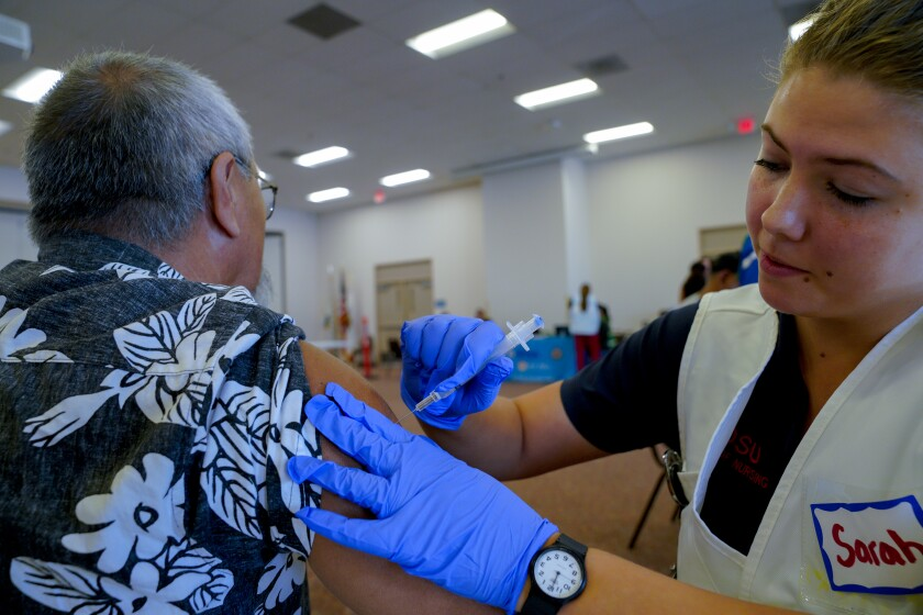 On Tuesday, October 15, 2019 Sarah Tomason was among the volunteers working with staff from The County of San Diego Health and Human Services Agency to provided free influenza and hepatitis A vaccinations to the public at the Martin Luther King Jr. Community Center in National City. Receiving his flu vaccination is George David, 63 from San Diego.