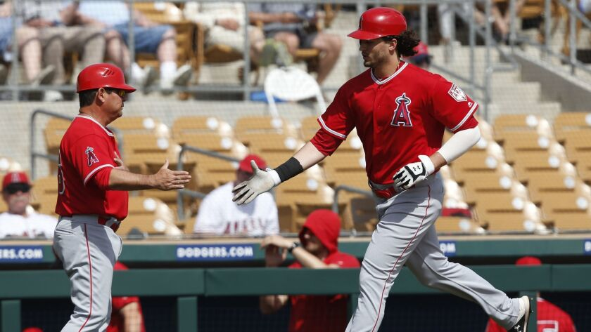 Los Angeles Angels' Jarrett Parker, right, is congratulated by third base coach Mike Gallego, left,