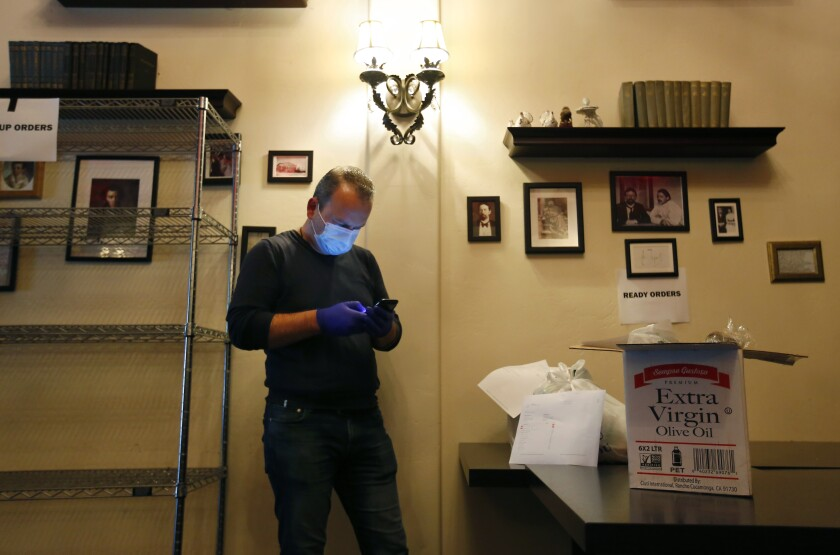 Arthur Gazaryan, who is normally a chef at Pushkin Russian Restaurant in downtown San Diego, looks at his phone as he gets ready to make a delivery of items the restaurant is now selling.