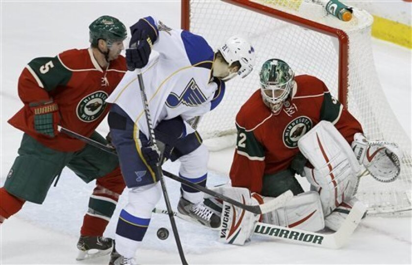 Minnesota Wild goalie Niklas Backstrom (32) of Finland covers the net as St. Louis Blues center Patrik Berglund, center, and Minnesota Wild defenseman Brett Clark (5) try to get control of the puck during the first period of an NHL hockey game in St. Paul, Minn., Monday, April 1, 2013. (AP Photo/An