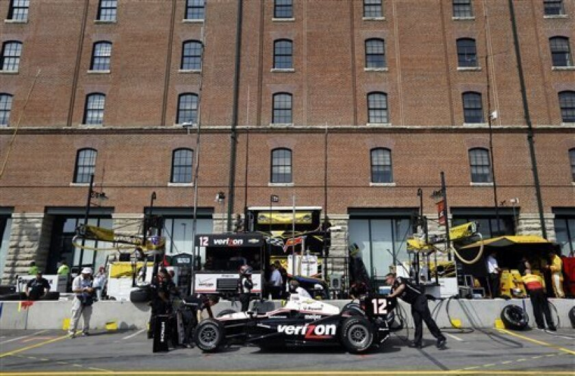 Pit crew members make adjustments to driver Will Power's car in front of the B&O Warehouse, part of Oriole Park at Camden Yards, during a practice session for the IndyCar Grand Prix of Baltimore auto race, Friday, Aug. 30, 2013, in Baltimore. (AP Photo/Patrick Semansky)