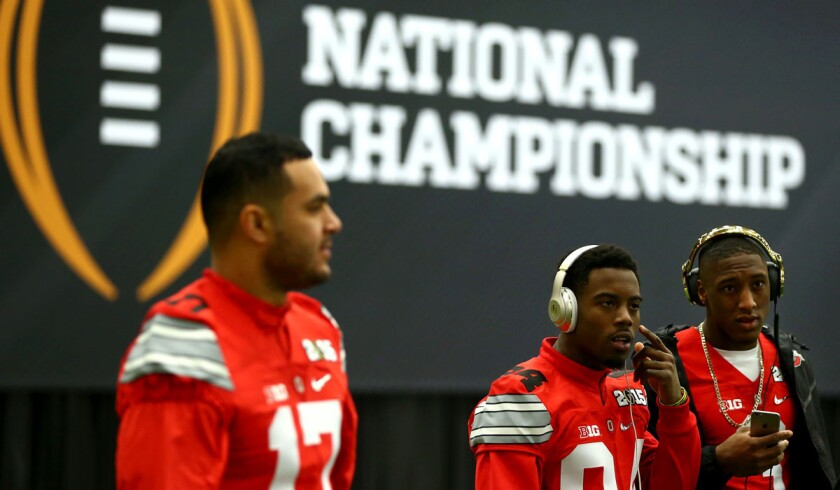 Ohio State players (from left) Jalin Marshall, Corey Smith and Michael Thomas arrive for the College Football Playoff media day on Saturday in Dallas.