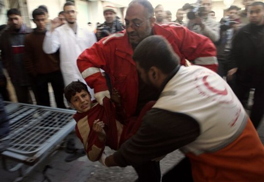 In this Jan. 6, 2009 file photo, Palestinians carry a wounded boy who according to Palestinian medical sources was injured in Israeli forces' operations in Gaza, to Shifa hospital in Gaza City. (AP Photo/Hatem Moussa, File)