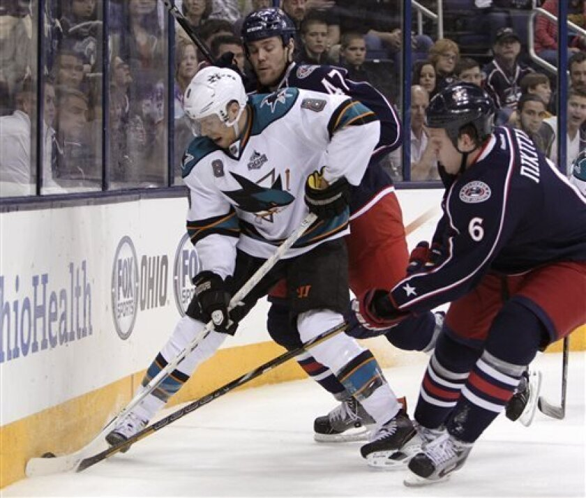 San Jose Sharks' Joe Pavelski, left, keeps the puck away from Columbus Blue Jackets' Dalton Prout, center, and Nikita Nikitin, of Russia, during the first period of an NHL hockey game Tuesday, April 9, 2013, in Columbus, Ohio. (AP Photo/Jay LaPrete)