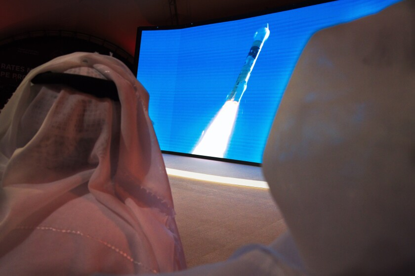 """FILE - In this Monday, July 20, 2020 file photo, men watch the launch of the """"Amal"""" or """"Hope"""" space probe at the Mohammed bin Rashid Space Center in Dubai, United Arab Emirates. The orbiter is scheduled to reach Mars on Tuesday, Feb. 9, 2021, followed less than 24 hours later by China's orbiter-rover combo. NASA's rover will arrive on the scene a week later, on Feb. 18, to collect rocks for return to Earth _ a key step in determining whether life ever existed at Mars. (AP Photo/Jon Gambrell)"""