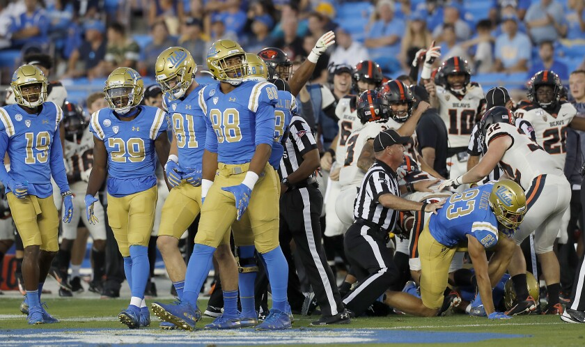 UCLA players walk off the field after Oregon State recovers a fumble on a Bruins kick return during Saturday's game.