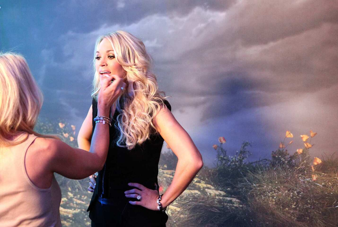 Carrie Underwood gets her makeup touched up before posing for fan pictures backstage prior to her concert at Staples Center Oct. 16, 2012.