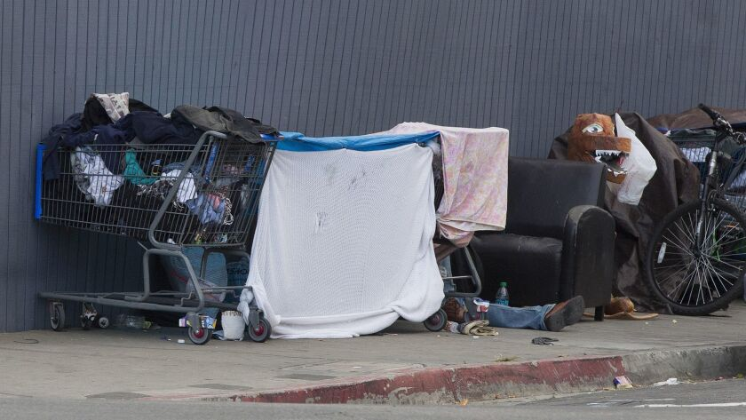Homeless people along Commercial Street in the Downtown area set up makeshift tents before the sun sets.