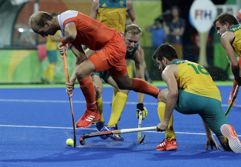 Netherlands' Billy Bakker, center, fight for the ball with Australia's Matt Ghodes, right, during a men's field hockey quarterfinal match at 2016 Summer Olympics in Rio de Janeiro, Brazil, Sunday, Aug. 14, 2016. (AP Photo/Hussein Malla)