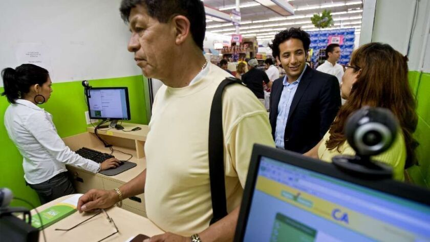 James Gutierrez, second from right, at a grocery store lending kiosk. His company, Insikt, makes loans of up to $2,500 through grocery stores and other businesses.