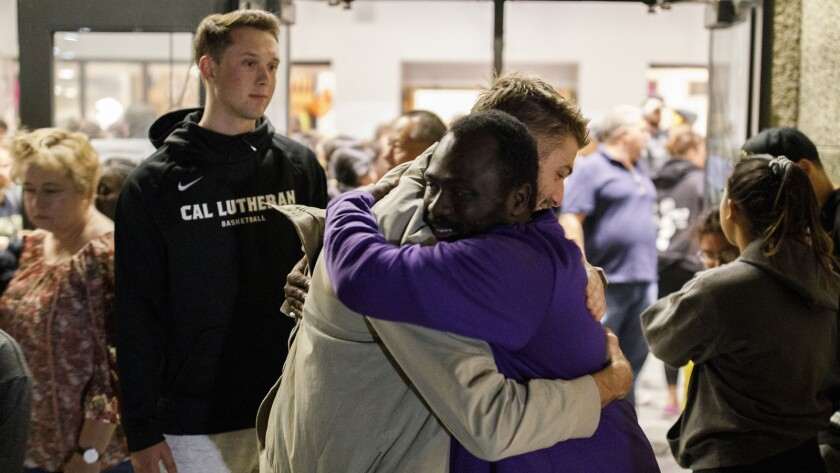 People embrace outside a vigil at the Samuelson Chapel on the Campus of Cal Lutheran University for