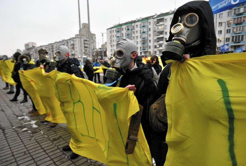 Protesters wearing gas masks hold Ukrainian national flags as they picket the Ukrainian House during a round table talks on Friday between Ukrainian President Viktor Yanukovych, former presidents and leaders of the opposition.