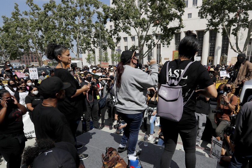 Melina Abdullah stands onstage as protesters rally outside the Hall of Justice in downtown Los Angeles