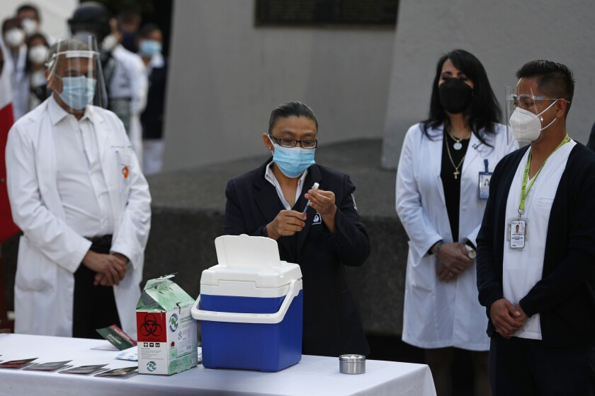 A health worker holds a vial of the COVID-19 vaccine in Mexico City