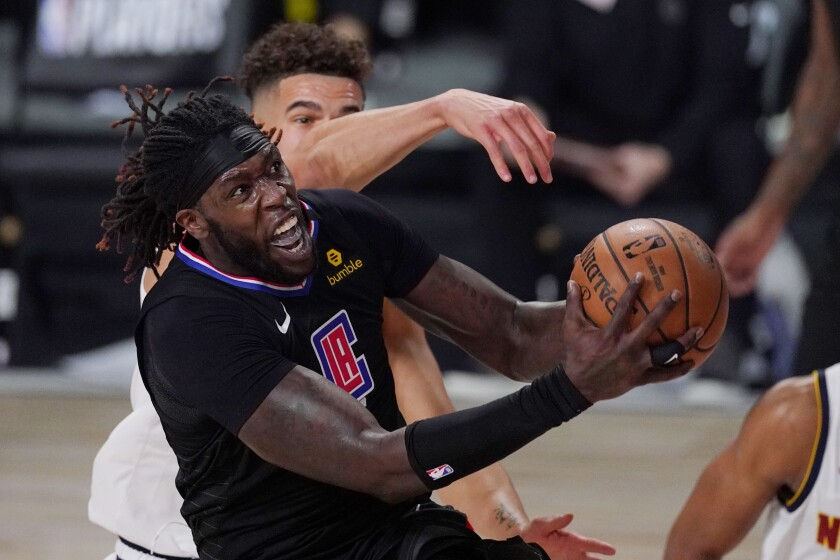 Clippers center Montrezl Harrell drives to the basket against Nuggets forward Michael Porter Jr. on Thursday.