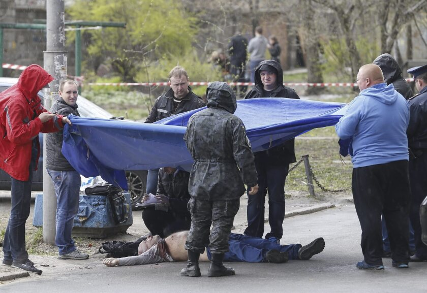 Ukrainian forensics workers prepare to move the body of slain journalist Oles Buzyna, who was gunned down in central Kiev on Thursday, the third critic of the Ukrainian leadership to be killed this week.