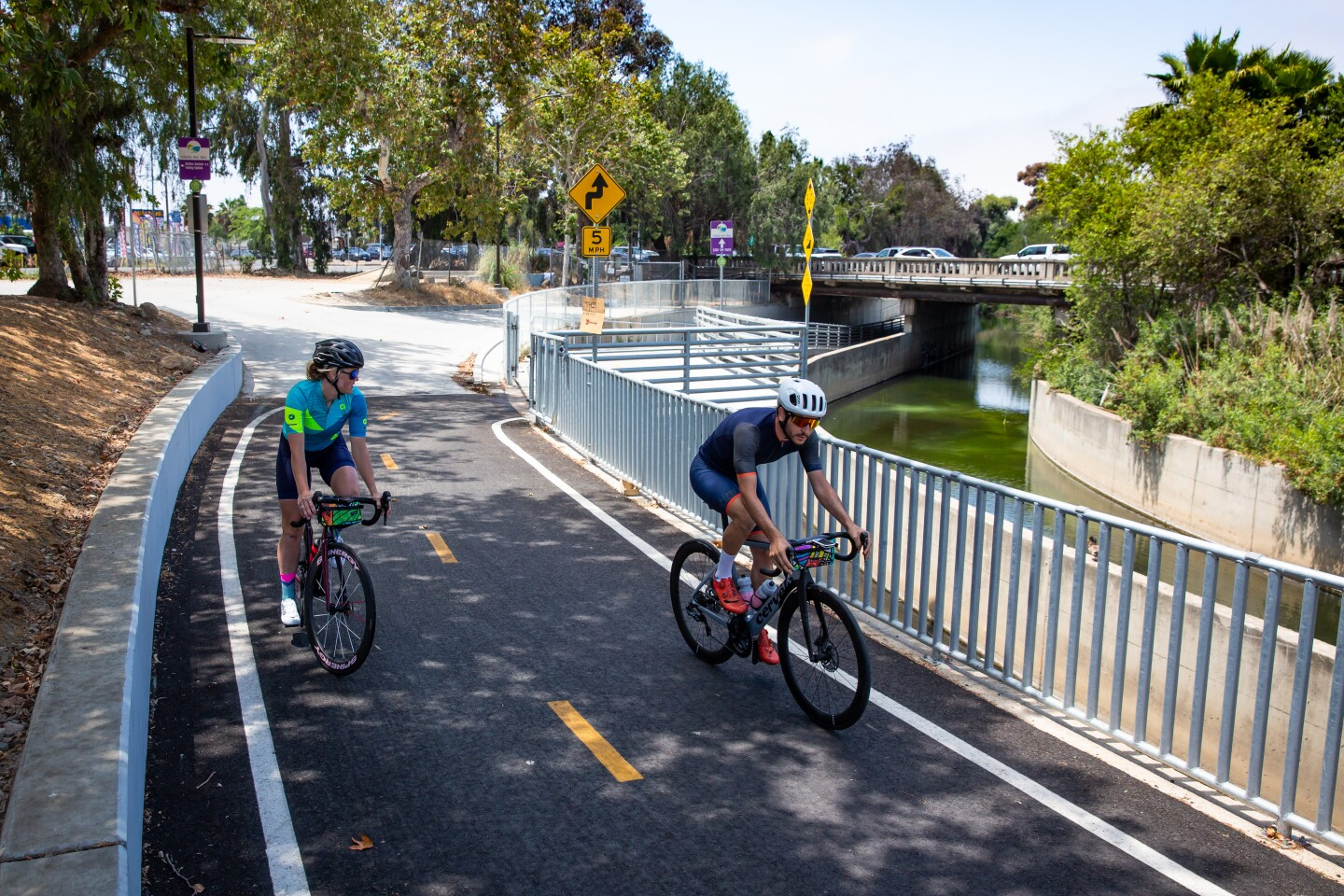 Gabe Canzi and Katherine Nadler ride along the Rose Creek Bikeway on June 27.