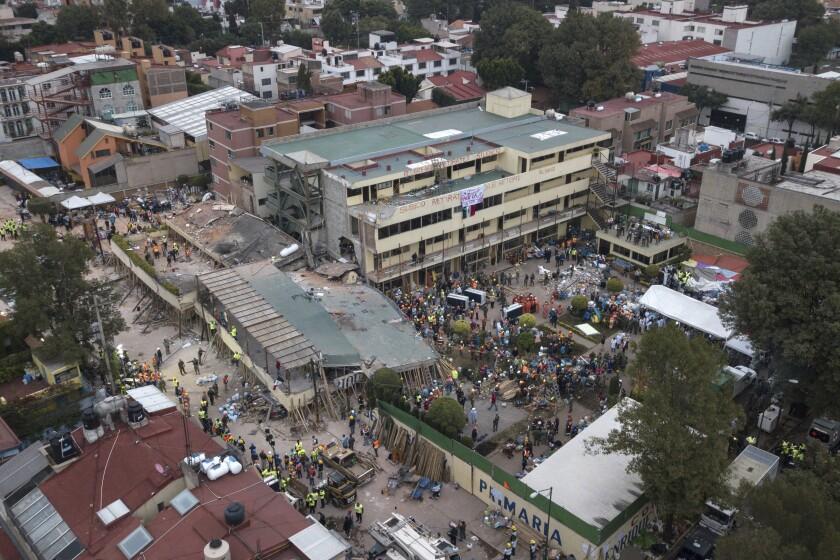 Voluntarios y socorristas intentan rescatar a niños atrapados tras el derrumbe de una escuela