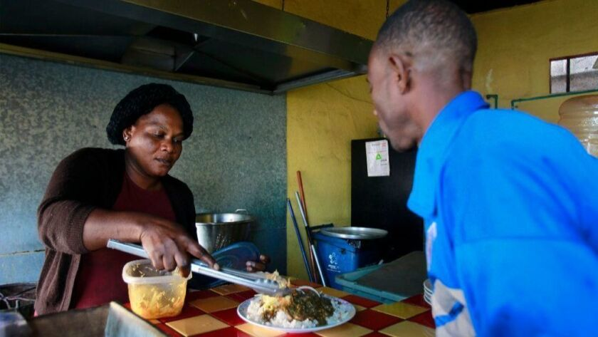Theresa Moise, who is from Haiti, serves Kesmer Mollisoint, also from Haiti, a plate of Haitian food at the Labadee restaurant where Moise works as a cook in Tijuana, Mexico on Wednesday.