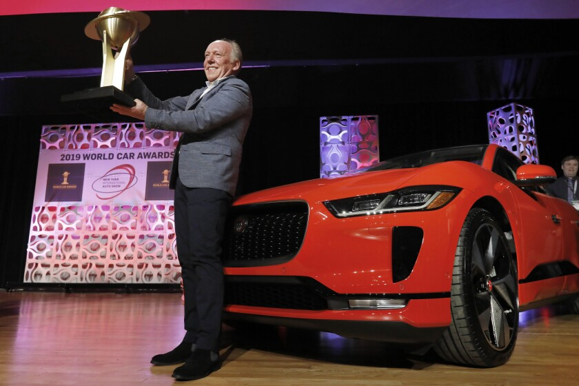 FILE - In this April 17, 2019 file photo, Jaguar Design Director Ian Callum raises the World Car of the Year trophy that was awarded to the Jaguar I-Pace, right, at the 2019 New York International Auto Show, in New York. The New York International Auto Show has become a casualty of the fast-spreading coronavirus delta variant. Show organizers said Wednesday, Aug. 4, 2021, that they've decided to cancel it this year, a little over two weeks before the scheduled start. (AP Photo/Richard Drew, File)